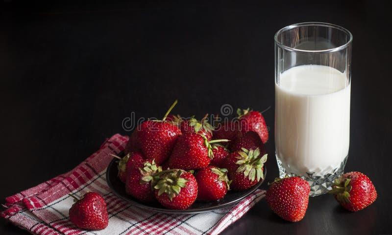 Fresa y un vidrio de leche fotos de archivo