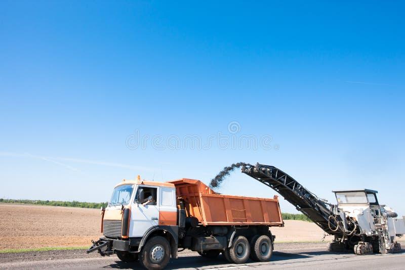 Fresadora que quita el aphalt machacado en el camión volquete imágenes de archivo libres de regalías