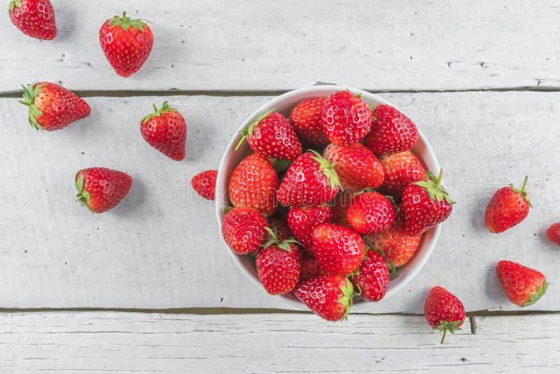 Fresas en cuenco en la opinión de sobremesa blanca fotografía de archivo