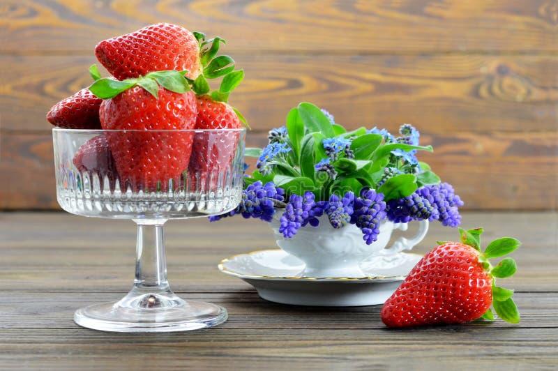 Fresas en las flores del vidrio y de la primavera fotos de archivo
