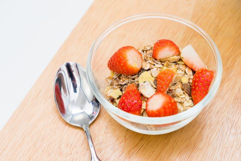 Fresas en un bol de vidrio con el cereal, en la tabla foto de archivo