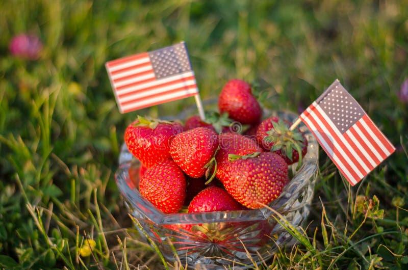 Fresas en un cuenco con las banderas americanas imágenes de archivo libres de regalías