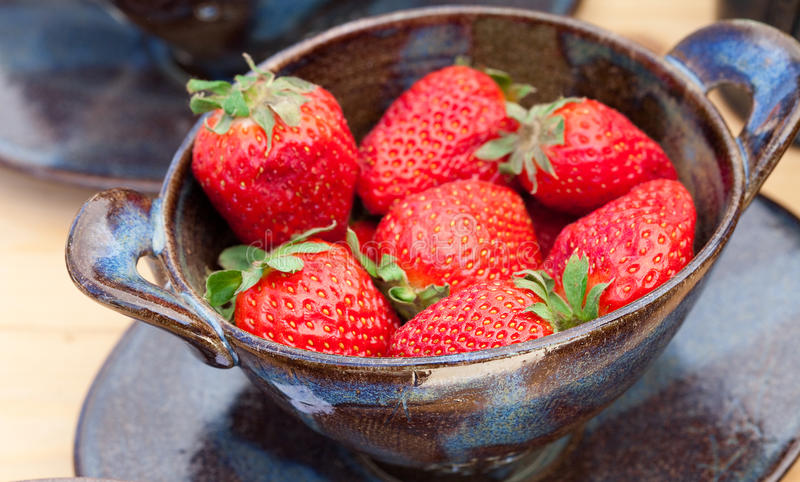 Fresas en un tazón de fuente de cerámica imágenes de archivo libres de regalías