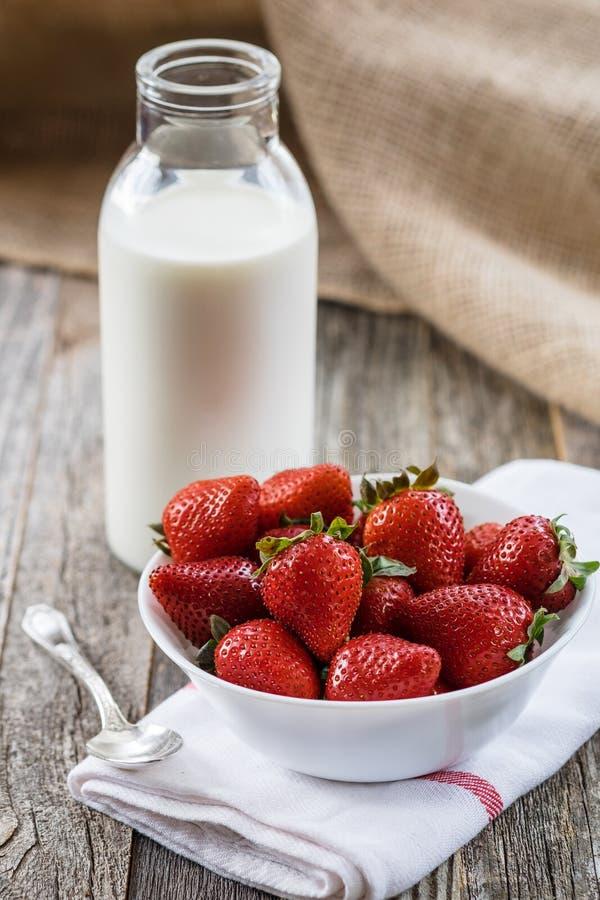 Fresas frescas con una botella de leche imagenes de archivo