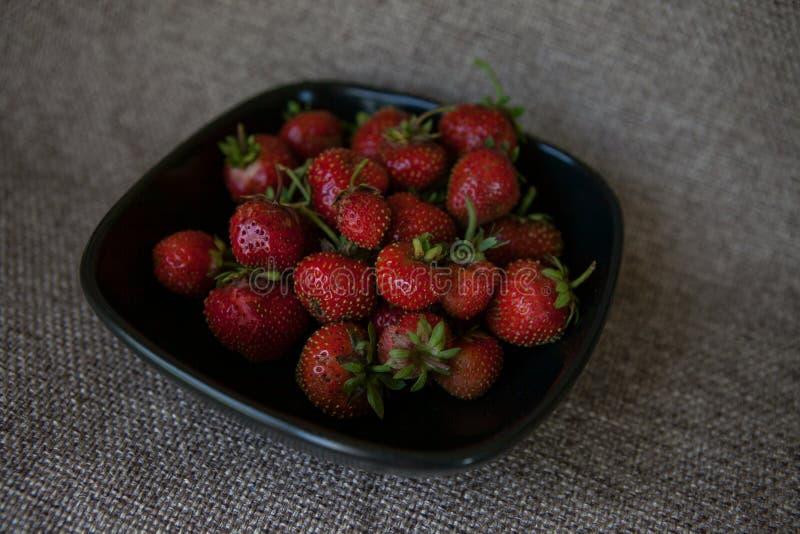 Fresas frescas en una placa negra imagen de archivo