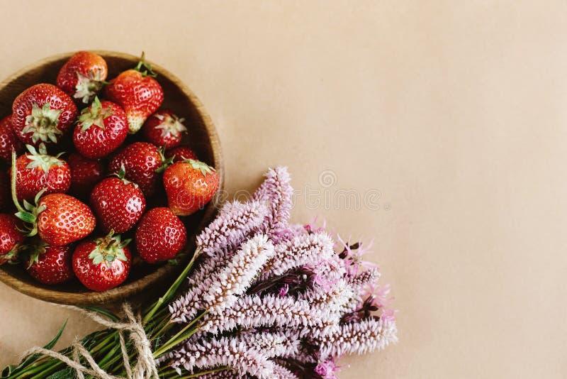 Fresas frescas hermosas y flores rosadas en backgroun del arte imágenes de archivo libres de regalías