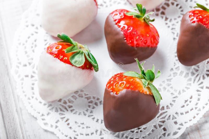 Fresas frescas sumergidas en chocolate oscuro y blanco en cierre ligero del fondo para arriba Barra deliciosa del postre y de car fotografía de archivo libre de regalías