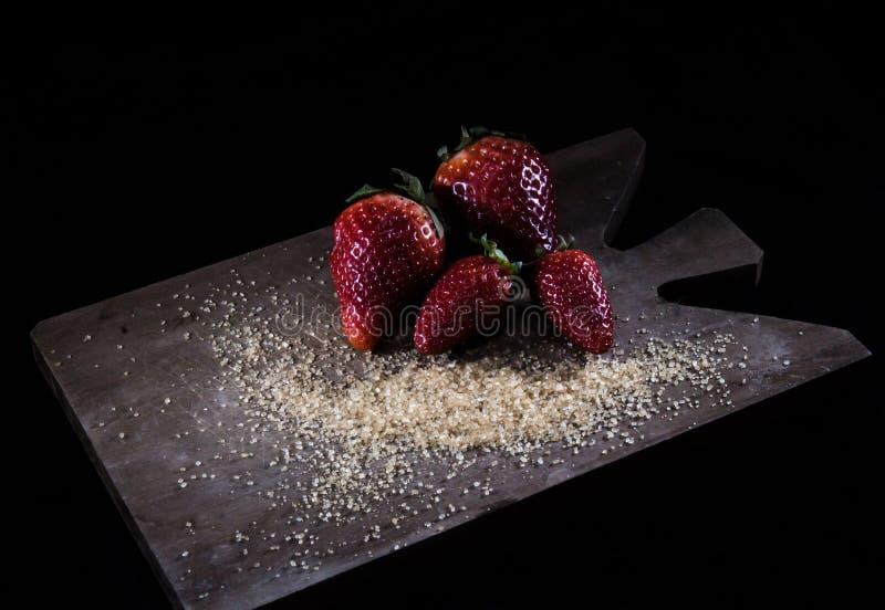 Fresas frescas y azúcar marrón imagen de archivo