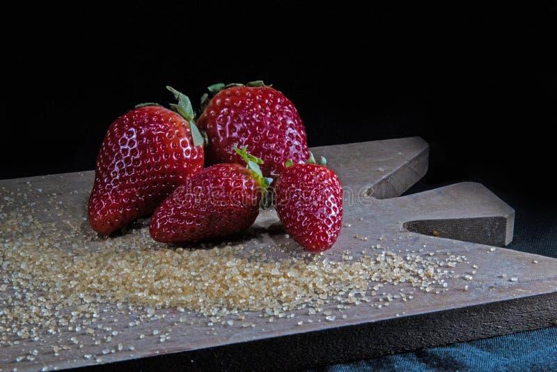Fresas frescas y azúcar marrón fotos de archivo