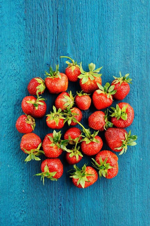 Fresas imperfectas frescas en forma redonda en backgro de la turquesa fotografía de archivo libre de regalías