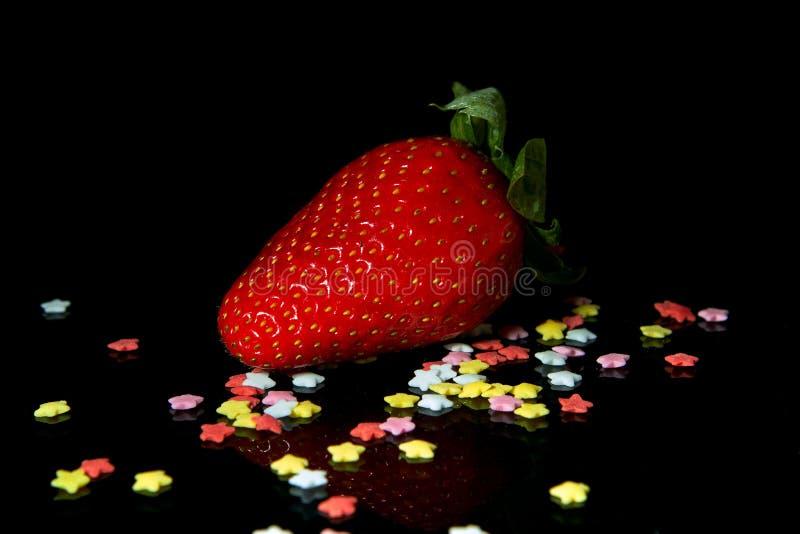 Fresas jugosas y maduras con los dulces en un fondo negro fotografía de archivo libre de regalías