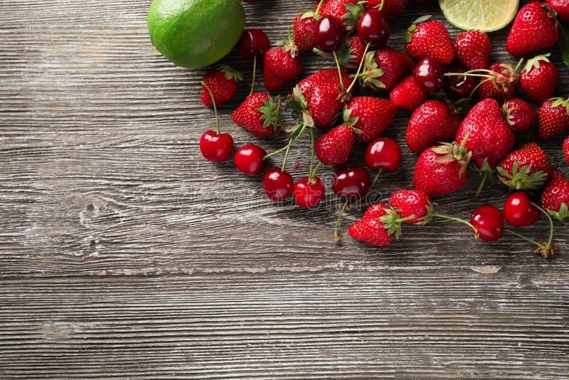 Fresas maduras con las cerezas y la cal en fondo de madera fotografía de archivo libre de regalías