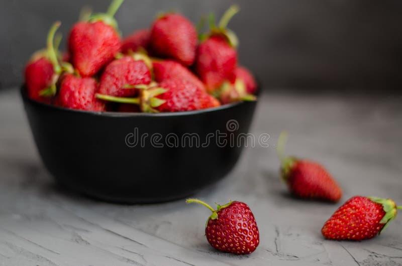 Fresas maduras del verano fresco en una placa negra en un fondo concreto gris imágenes de archivo libres de regalías