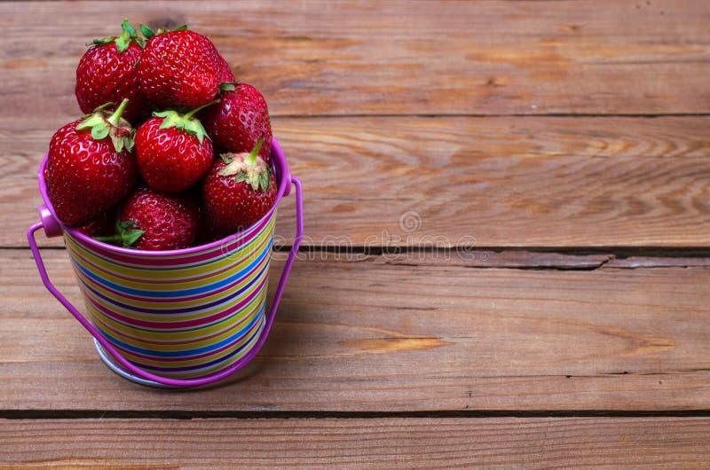 Fresas maduras en un cubo brillante en una tabla de madera, una copia o fotografía de archivo