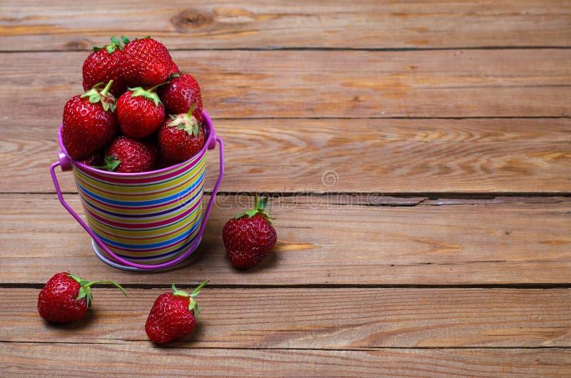 Fresas maduras en un cubo brillante en una tabla de madera, una copia o foto de archivo libre de regalías