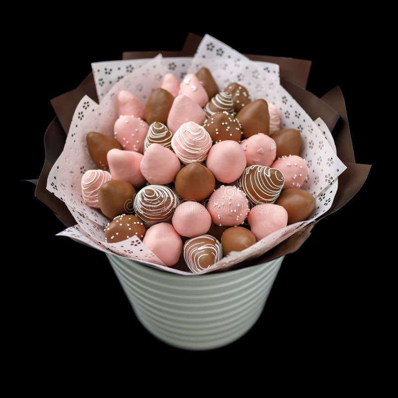 Fresas maduras sabrosas en chocolate marrón y rosado bajo la forma de ramo en un fondo negro imagenes de archivo