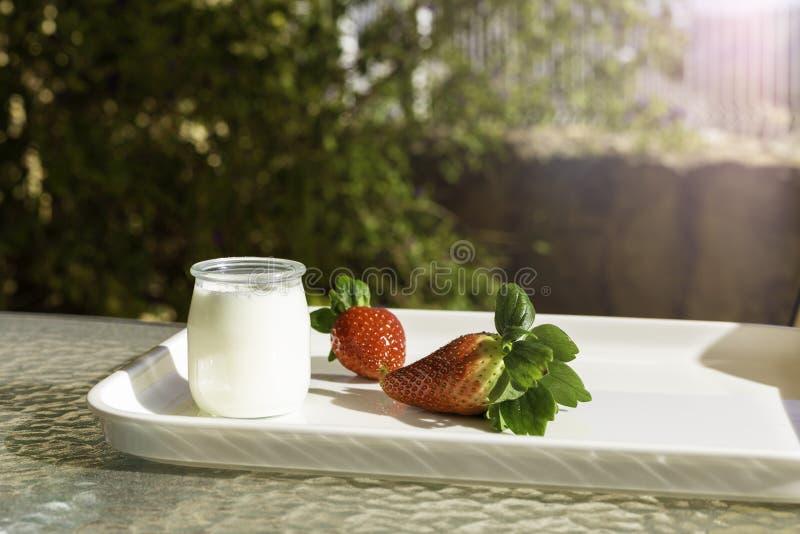 Fresas rojas frescas y yogur blanco en un tarro de cristal en una bandeja blanca en una tabla en el jardín o en la terraza en un  imagen de archivo libre de regalías