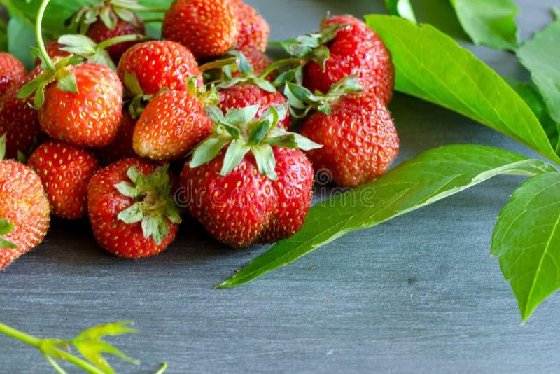 Fresas rojas maduras frescas en la tabla gris fotos de archivo