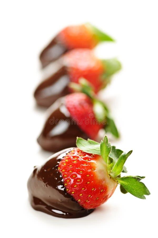 Fresas sumergidas en chocolate foto de archivo