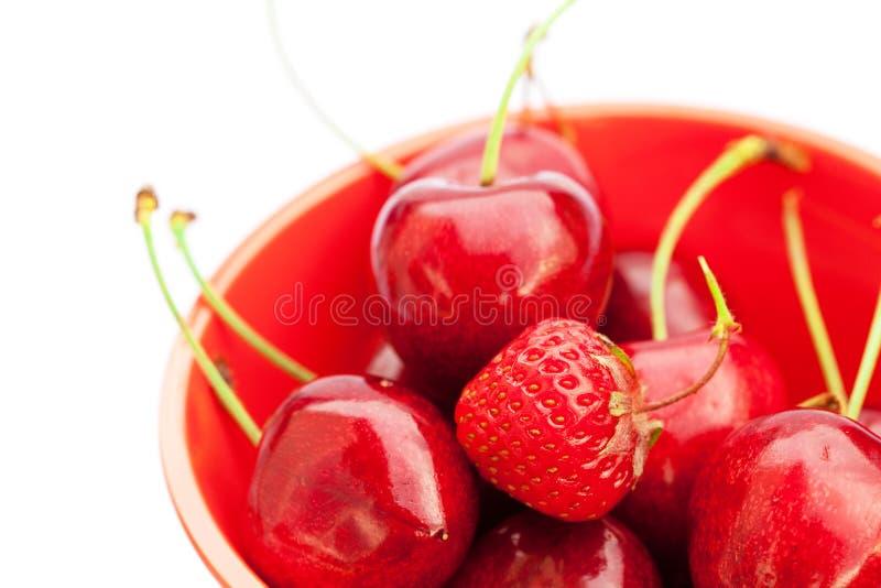 Fresas y cerezas en un tazón de fuente fotos de archivo