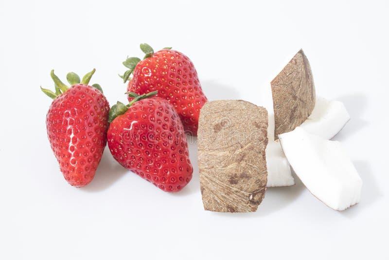 Fresas y composición del coco en un fondo blanco imágenes de archivo libres de regalías