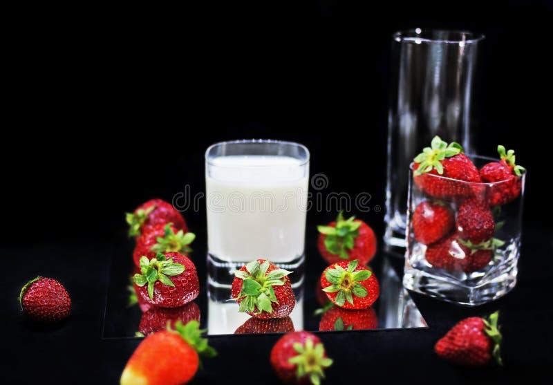 Fresas y vidrio rojos frescos de leche en fondo negro fotografía de archivo libre de regalías