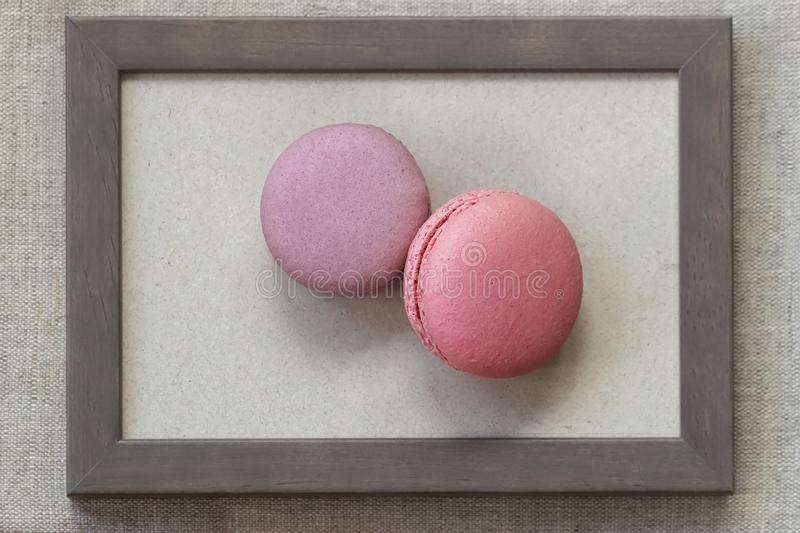 Fresch macaroons of pink and violet colors in wooden frame on wall, unusual abstract sweet art royalty free stock photography
