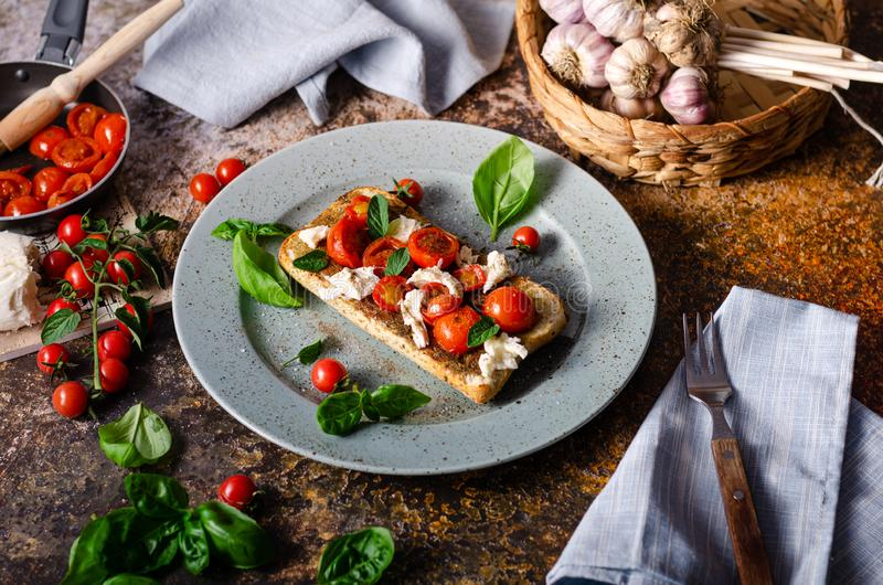 Bruschetta tomato mozzarella breakfast. Fresch and simple breakfast with grilled tomatoes, crispy bread and basil stock images