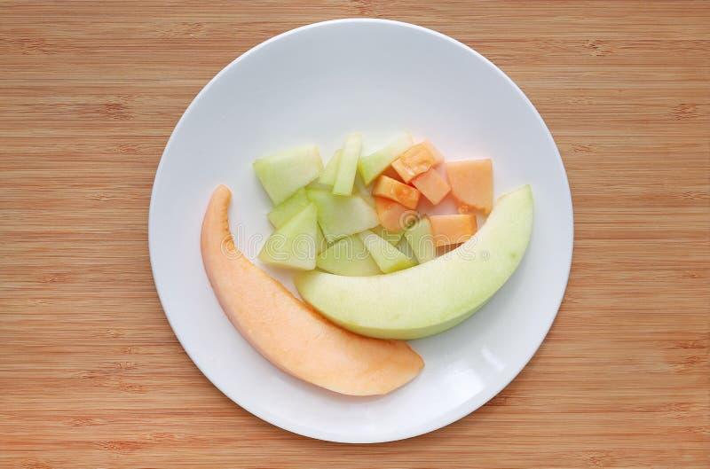 Fresco affettato del melone verde ed arancio del cantalupo sul piatto bianco contro il fondo del bordo di legno fotografia stock libera da diritti