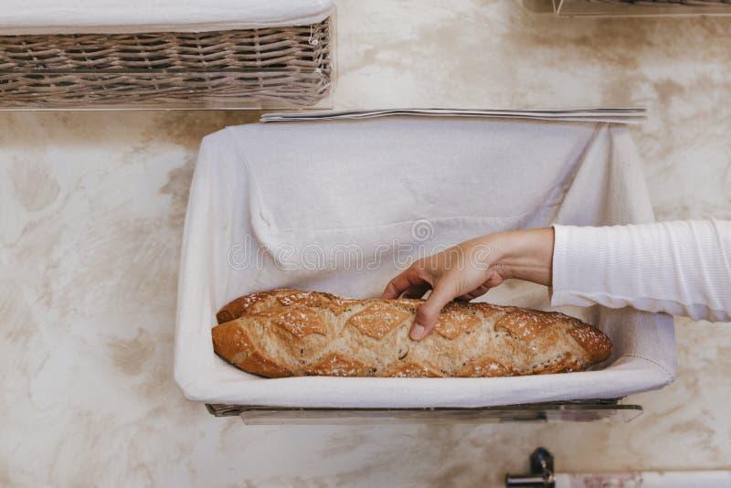 Fresco e caldo mano alta vicina della donna che tiene pane fresco e caldo appena dal forno Concetto del forno fotografie stock