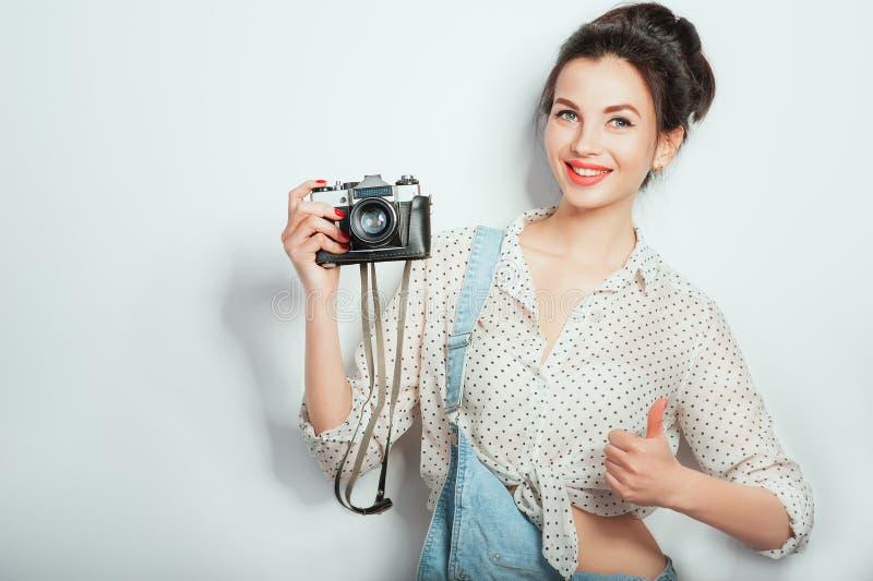 Fresco! Modello fresco grazioso della giovane donna con la retro macchina fotografica che dura in vestiti del denim che posano su fotografie stock libere da diritti