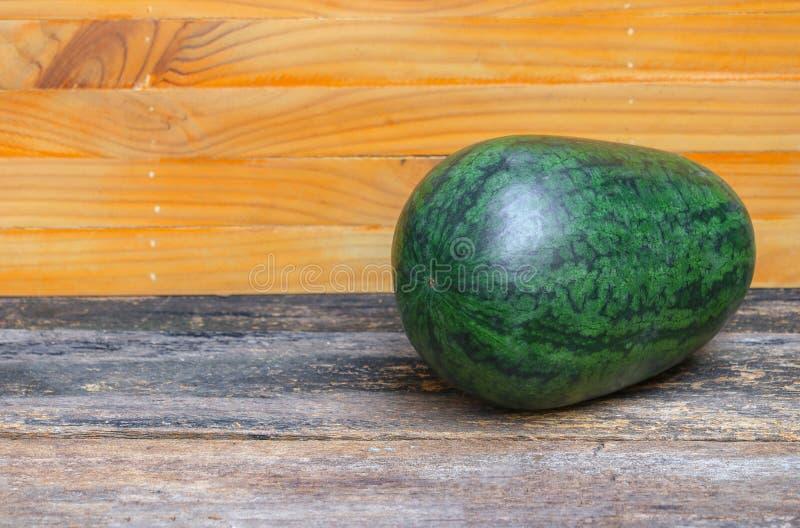 Fresco verde de la sandía del jardín en un fondo de madera marrón fotografía de archivo