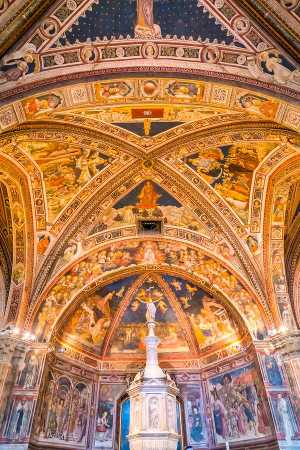Frescoes and The baptismal font inside the Siena Baptistery of San Giovanni royalty free stock image