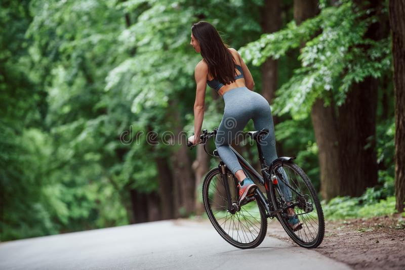 Fresh air. Female cyclist on a bike on asphalt road in the forest at daytime royalty free stock photo