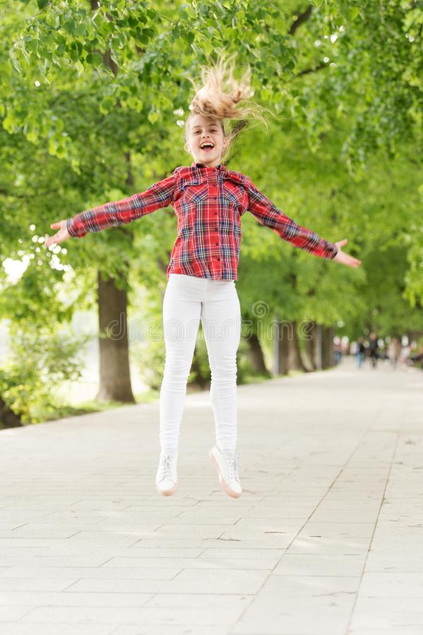 Fresh air gives her the vital energy. High energy or hyperactive kid. Small girl jumping in casual fit for energetic royalty free stock images