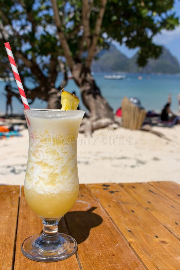 Fresh alcohol cocktail on the beach. Cold pina colada on seascape background. Cool pineapple cocktail with stick. Exotic resort. Fresh alcohol cocktail on the stock images