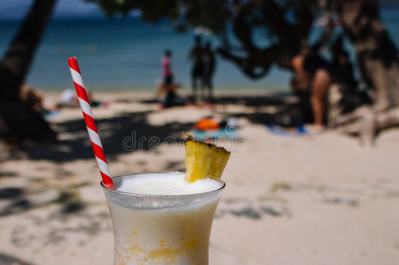 Fresh alcohol cocktail on the beach. Cold pina colada on seascape background. Cool pineapple cocktail with stick. Exotic resort. Fresh alcohol cocktail on the stock photography