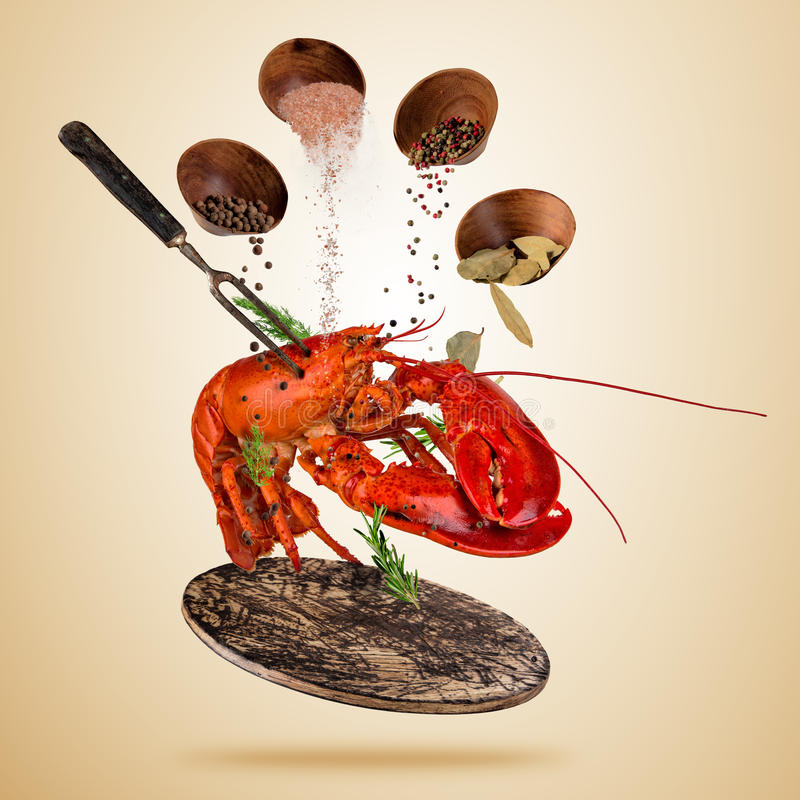 Fresh American lobster with falling spices, flying above wooden stock illustration