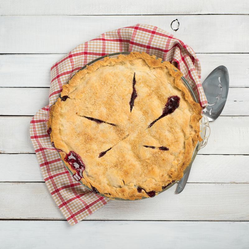 Free Fresh And Messy Baked Blackberry Pie With Red Plaid Towel And Server On White Shiplap Board Background Table With Square Crop And Royalty Free Stock Images - 122389599