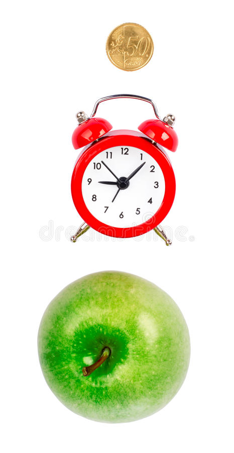 Fresh apple with alarm clock. And coin on isolated white background stock photo
