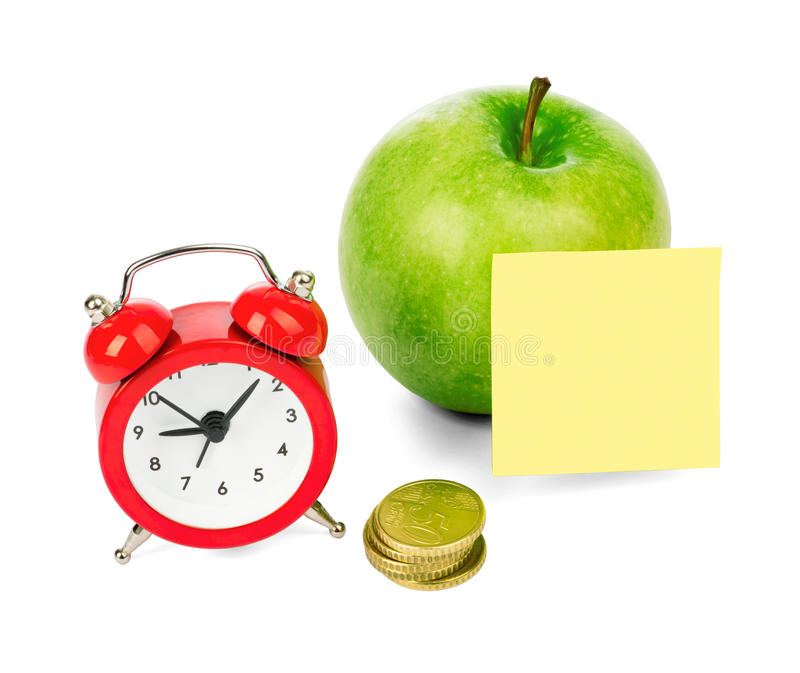 Fresh apple with alarm clock. And gold coins on isolated white background, close up royalty free stock image