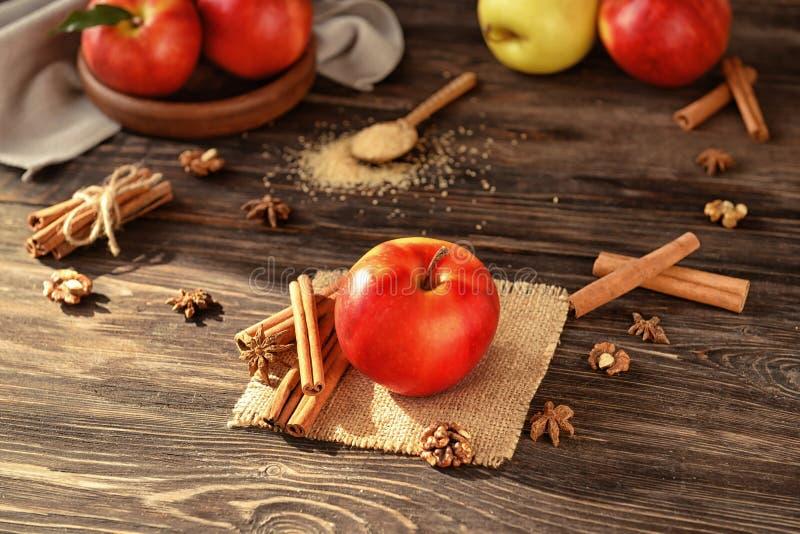 Fresh apple and cinnamon sticks on wooden table stock photo
