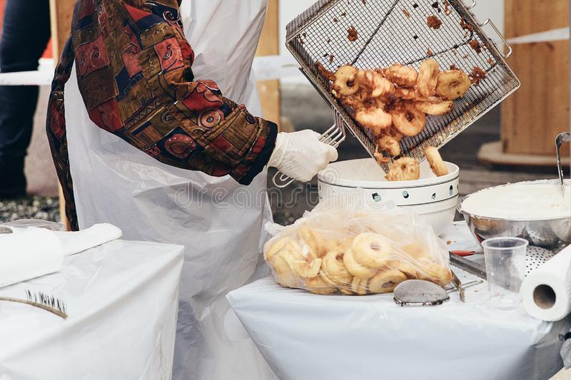 Fresh apple fritters being transferred into a bowl to be sprinkled with cinnamon sugar. Favourite snack on Christmas market. royalty free stock photography