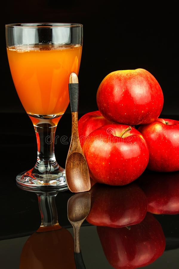 Fresh apple juice in a glass. Fruit harvest. Healthy beverage. Apples on the kitchen table. Production of juice. On a black backgr stock image