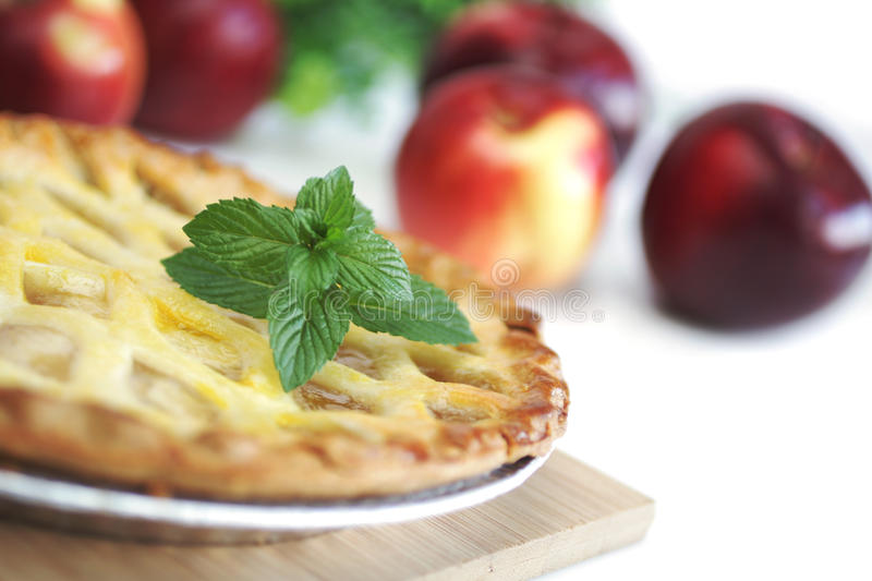Fresh apple pie. Whole apple pie with red apples in background stock image