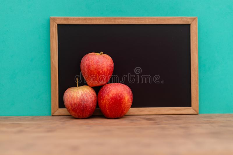 Fresh apple red with chalkboard on wooden table on blue background. copy space royalty free stock image