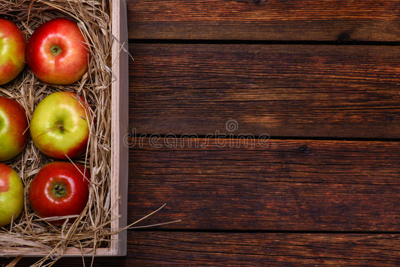 Fresh apples in box on wooden table with copy space royalty free stock photos