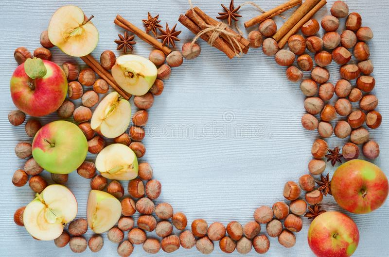 Fresh apples, hazelnuts and spices - anise stars and cinnamon on the gray kitchen table. Ingredients for autumn pie or mulled wine royalty free stock image