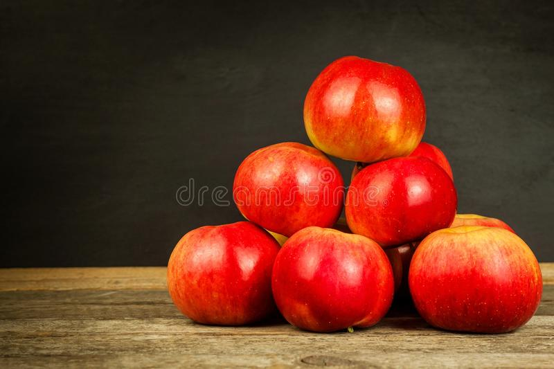 Fresh apples on an old wooden table. Black background. Autumn harvest of fruit. Sales of apples. Life on the farm. Food photograp stock images