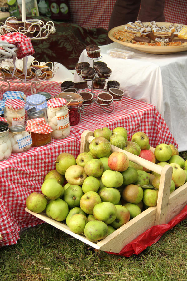 Fresh apples and preserves. Fresh green apples in a wooden basket in front of a table set with beautiful treats and preserves stock images